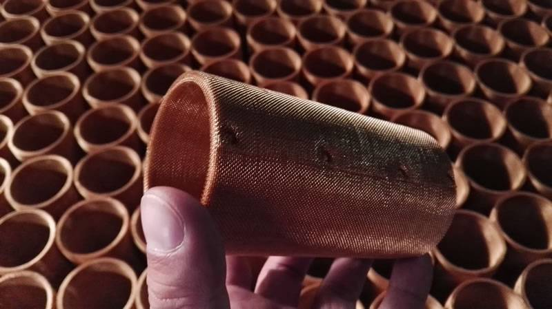 A hand is holding a spot welded copper mesh roll, and there are more of them on the back.