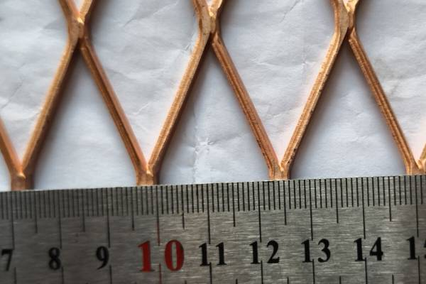 A ruler is measuring the short way of opening of the expanded mesh.