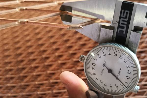 A ruler is measuring the thickness of the expanded mesh.