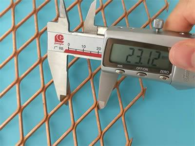 A callipers is measuring the SWD of a copper expanded mesh.