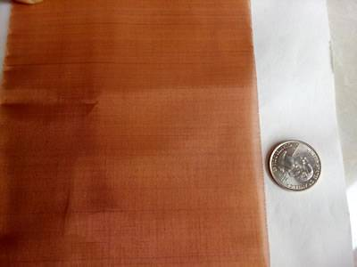 A piece of copper mesh is beside a metal coin.